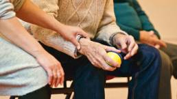 Picture of a younger woman gently holding on to an older man's wrist in a nursing home. Image is being used for a blog about How to Choose the Right Nursing Home in Tampa.