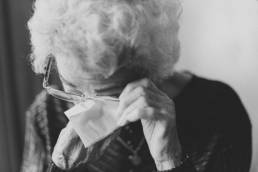 Black and white photo of an elderly woman wiping her eyes with a tissue. Image being used for a blog about nursing home abuse.
